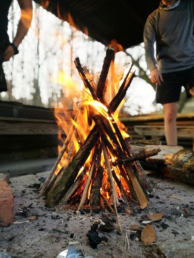 Man standing by burning campfire at campsite