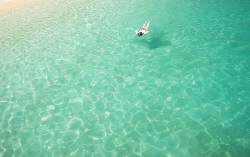 Woman snorkling and relaxing crystal clear and turquoise sea water of the tropical sea . Bay Beach Beautiful Bikini Blue Body Care Carefree Caribbean Coast Enjoy Female Girl Happiness Happy Healthy Holiday Human Island Lady Landscape Laying Leisure Life Lifestyle Nature Ocean People Pleasure Relax Relaxation Resort Rest Sand Sea Seascape Seashore Seaside Shore Snorkling Summer Sunbathing Swim Travel Tropical Vacation View Woman