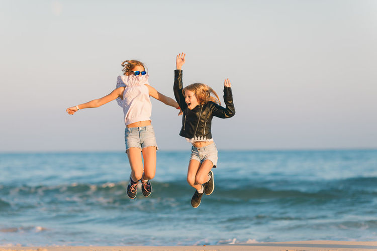 Two young girls jumping happily on a beach in Spain Sea Water Fun Full Length Human Arm Leisure Activity Togetherness Emotion Real People Lifestyles Two People Bonding Horizon Over Water Positive Emotion Happiness Arms Raised Jumping Seaside Beach Girls Tween Age Children