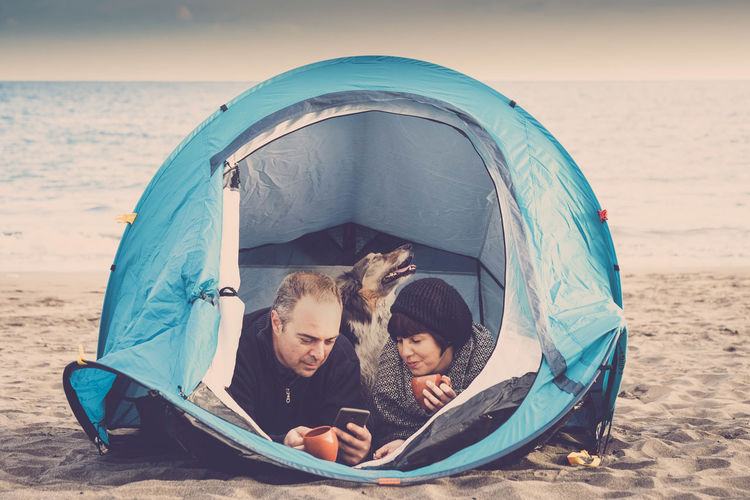 Couple with dog resting in tent at beach