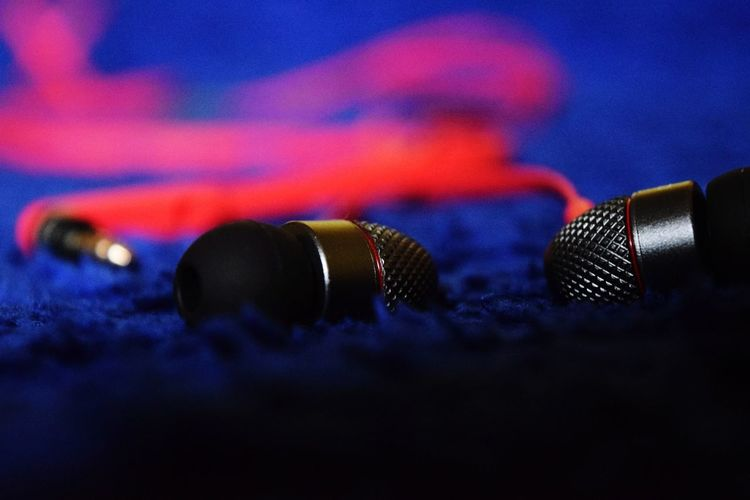 Close-Up Of In-Ear Headphones On Rug