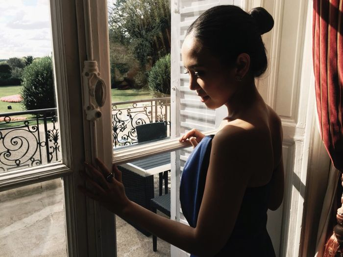 Side view of young woman standing by window