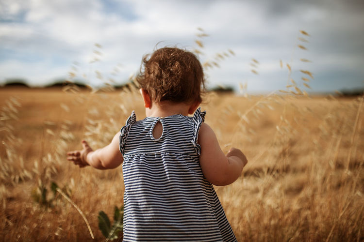 Rear view of cute baby standing on land against sky