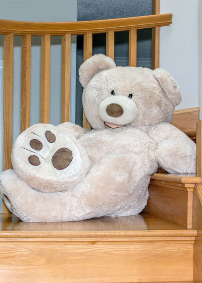 A large giant teddy bear lounges on a wood stair case Bear Humor Stairs Animal Representation Close-up Cuddely Toy Cute Day Furniture Giant Bear Home Interior Indoors  Indoors  No People Representation Seat Softness Staircase Still Life Stuffed Stuffed Toy Teddy Bear Toy Wood Wood - Material