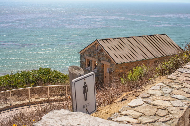 High angle view of sign against public restroom and sea on sunny day