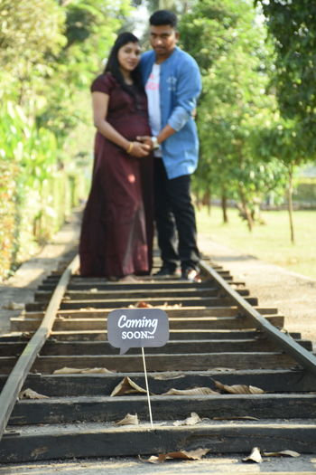 Rear view of couple standing on railroad tracks