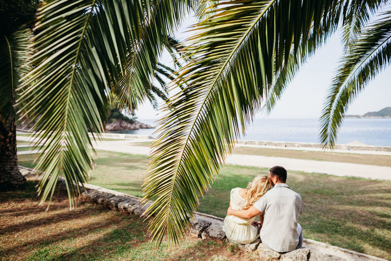 Rear View Of Couple Sitting By Sea