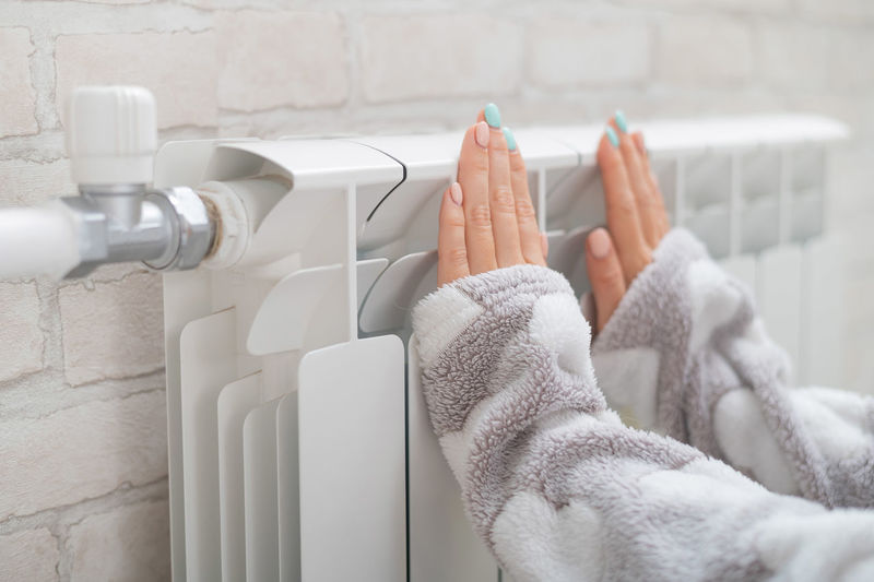 Woman touching thermostat on wall