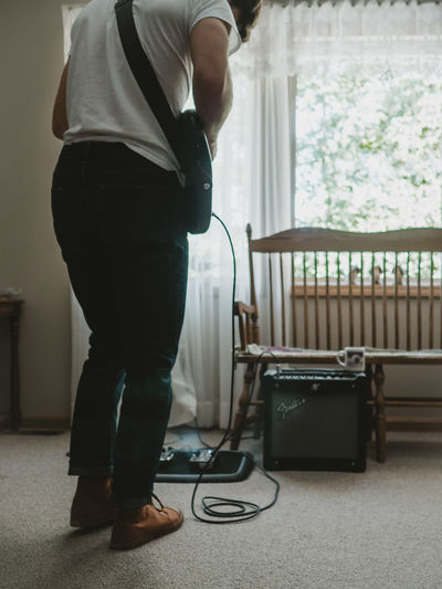 Low section of man holding guitar at home