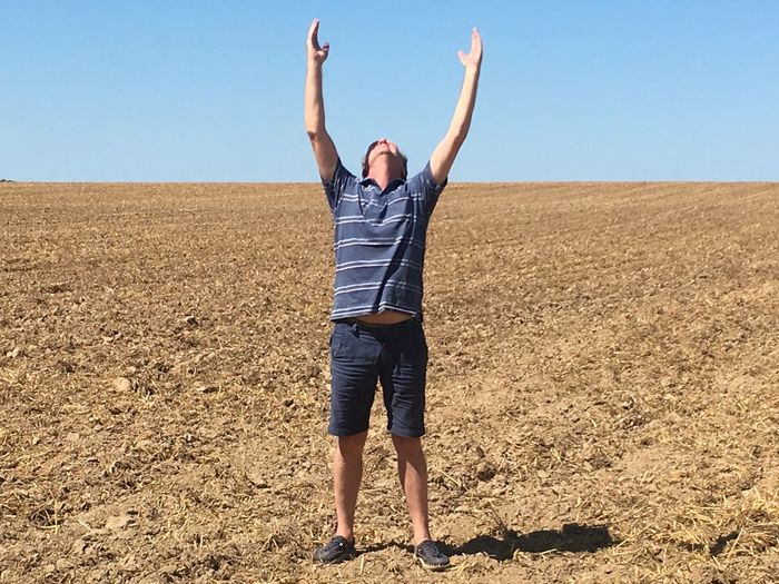Full length of man with arms raised standing on field