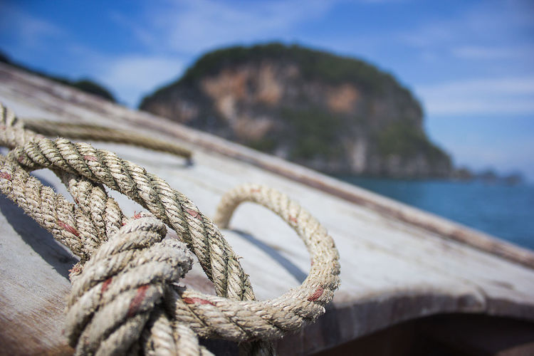 Close-Up Of Tied Rope On Boat In Sea Against Mountain