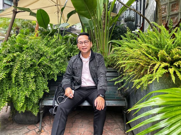 Portrait of mature man sitting on bench against plants