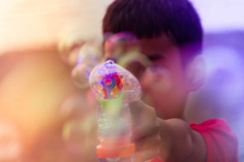 A kid playing bubbles Bubbles Childhood One Person Headshot Holding Bubble Wand Indoors  Child Elementary Age Multi Colored Children Only Close-up Real People