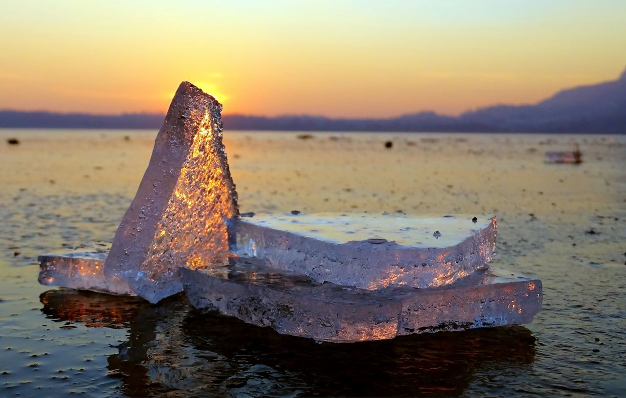 Close-Up Of Ice Cubes At Beach During Sunset