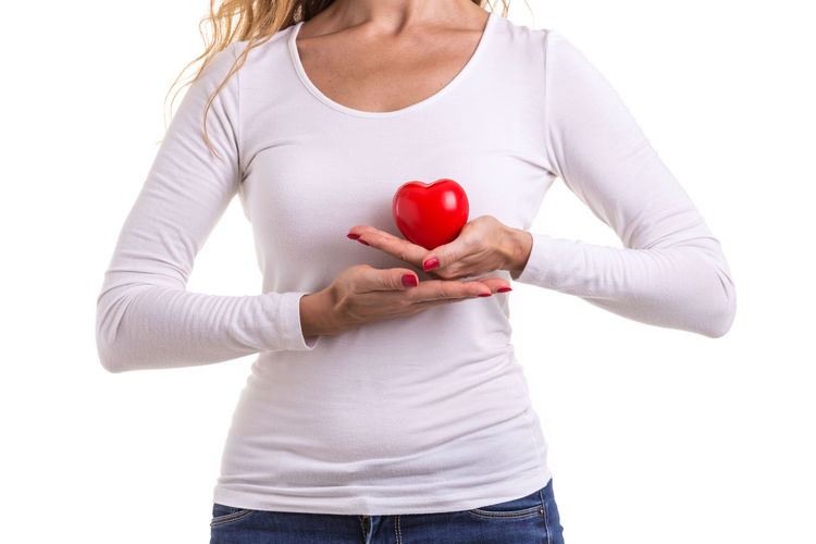 Midsection of woman holding heart shape against white background