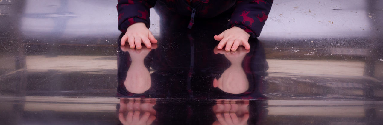 A toddlers hands reflecting on a metal slide