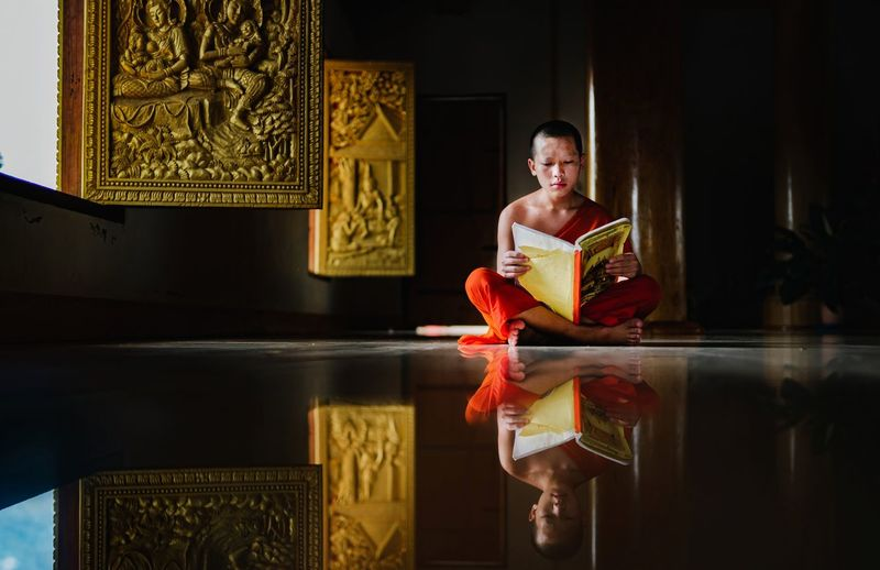 Monk reading book while sitting on floor in monastery