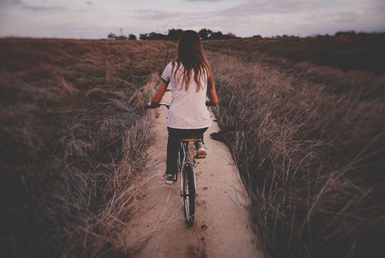 Rear view of girl cycling amidst plant during sunset