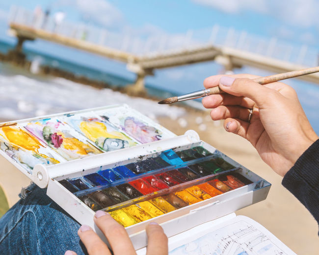 The girl draws with watercolors on the coast Human Hand Artist Painter - Artist Close-up Outdoors Retirement People Human Body Part Holding Leisure Activity One Person Adults Only Woman Watercolor Brush