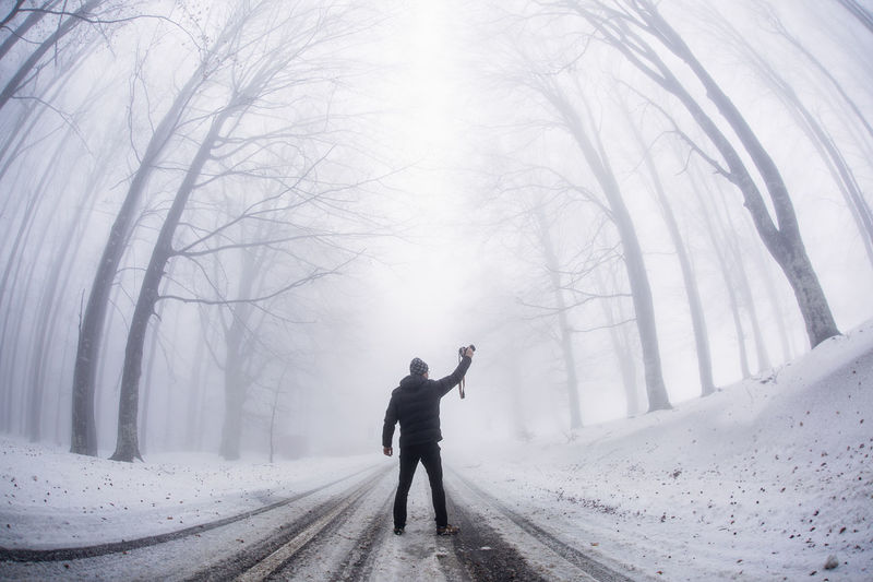 Full length of man on snow covered road during winter