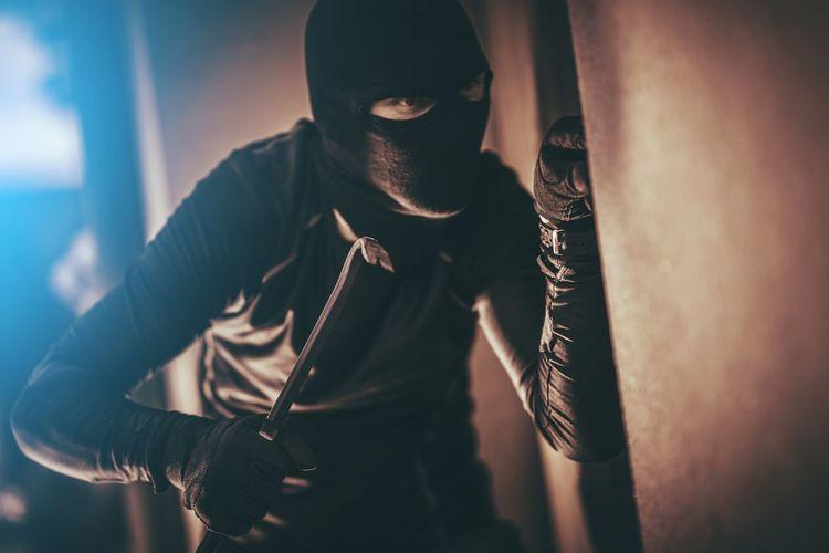 Burglar looking by wall