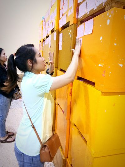 Side view of woman sticking adhesive note on crate