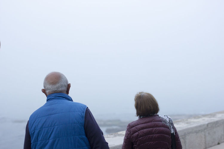 Rear View Of Man And Woman Looking At Sea From Footpath