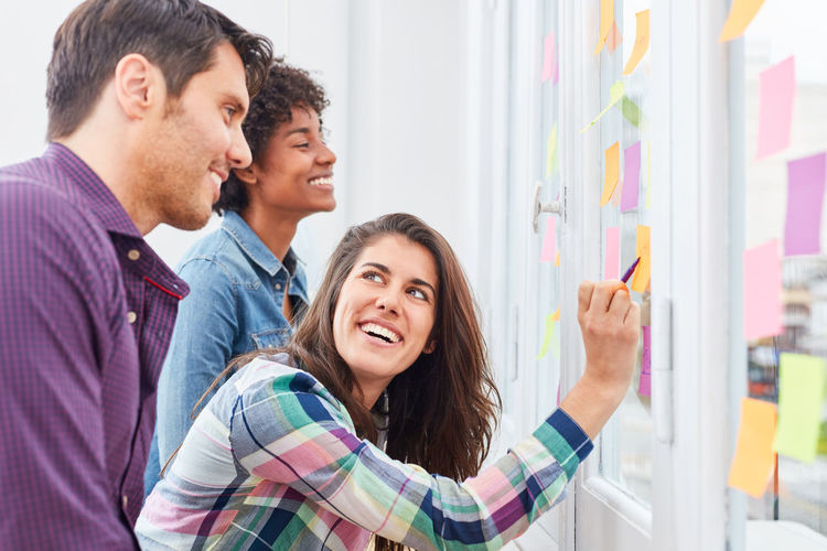 Smiling businesswoman pointing at adhesive note on glass while standing with colleagues