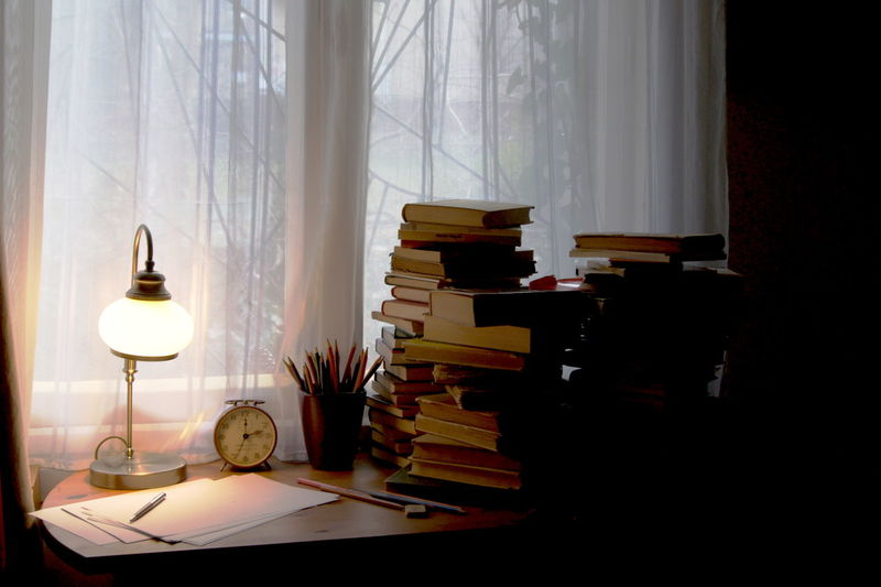 Books And Illuminated Lamp On Desk At Home