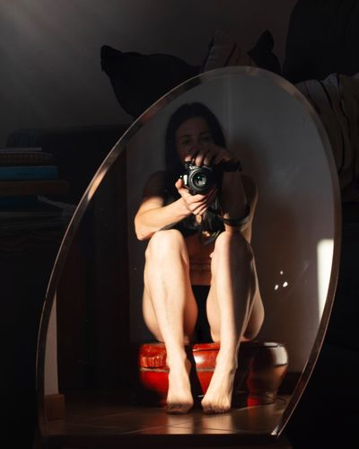 Woman with camera reflecting on mirror at home