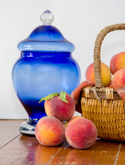 peaches in a basket and a blue jar on white Agriculture Basketball Fall Colors Freshness Nature USA Basket Blue Jar Container Food Food And Drink Freshness Fruit Healthy Eating Indoors  Juicy Fruit Michigan Peaches Orange Color Organic Peanuts Peach Still Life Table Wellbeing Wood - Material Yellow