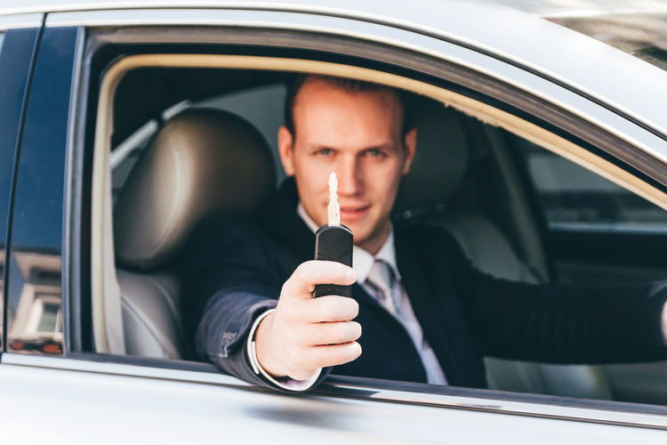 Portrait of businessman holding key while sitting in car