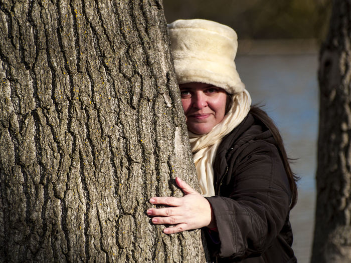 Portrait Of Woman Embracing Tree Trunk