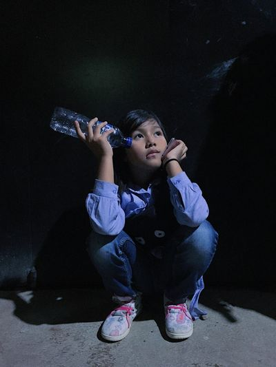 Thoughtful girl with bottle crouching against wall