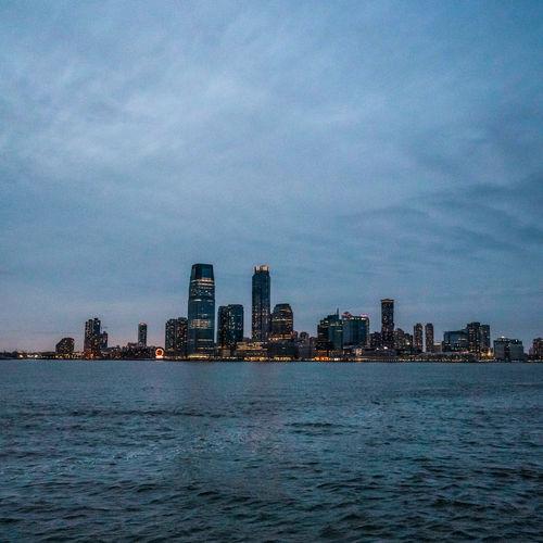Sea by buildings against sky at dusk