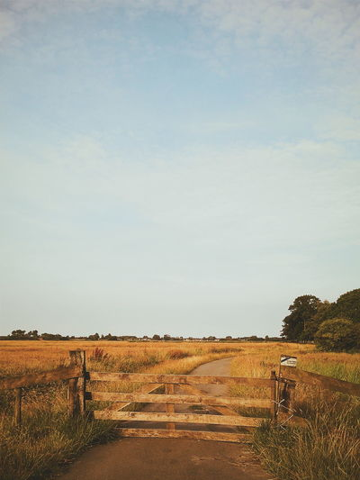 Closed wooden gate on road amidst grassy field against sky