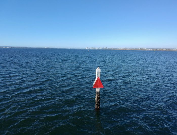 A lone sign post by the ocean
