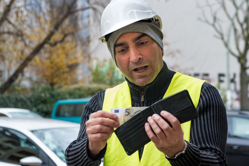 Engineer in reflective clothing looking at wallet
