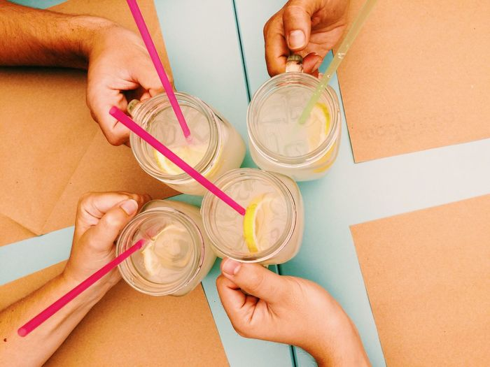Cropped image of friends holding lemonade jars at table