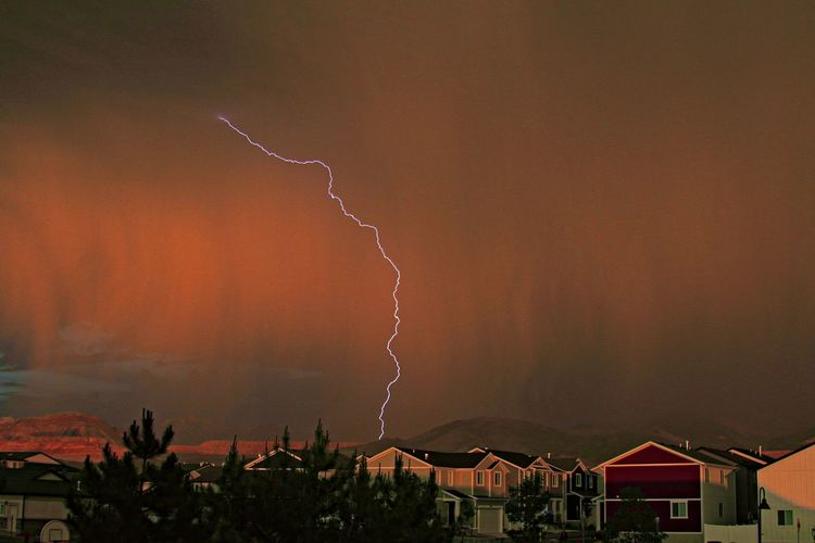 Low angle view of lightning against sky during sunset