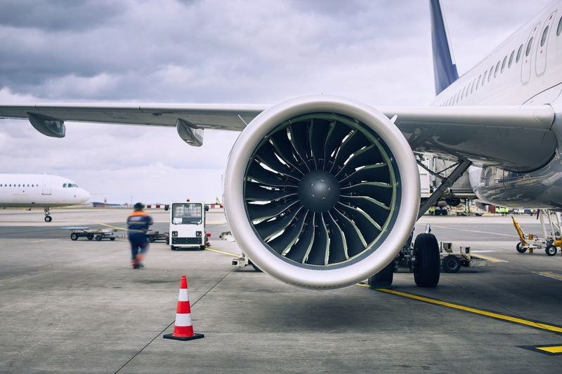 Busy day at airport. Ground crew preparing airplane before flight.Travel and industry concepts. Airplane Airport Airport Runway Preparation  Handling Aircraft Engine Jet Engine Flight Aviation Transportation Worker Air Vehicle Travel Aircraft Wing Aerospace Industry Real People Journey Working Service Loading Staff Flying Departure Travel