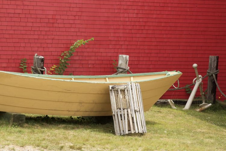Wooden boat moored against red brick wall