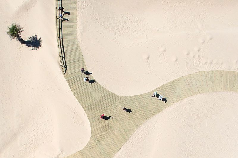 High angle view of people walking on boardwalk at desert during sunny day