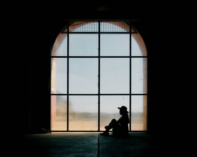 Side view of a silhouette man sitting against window in building