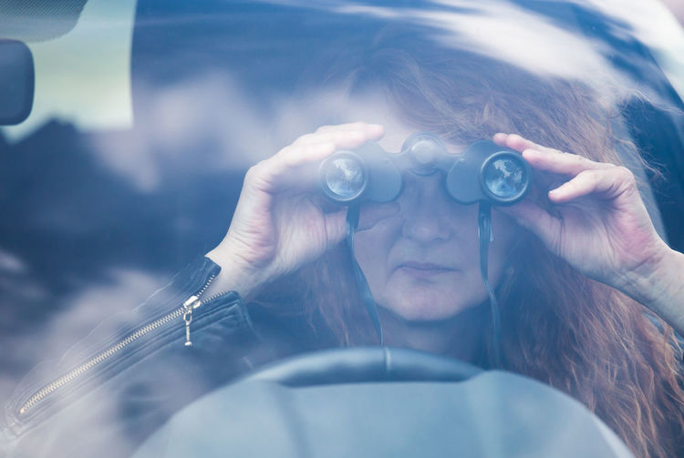 Close-up of woman looking through binoculars while sitting in car
