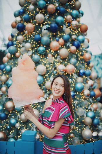 Portrait of smiling young woman standing by christmas tree holding cotton candy outdoors