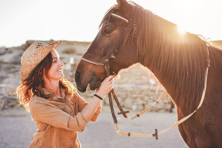 Smiling woman holding horse saddle against clear sky