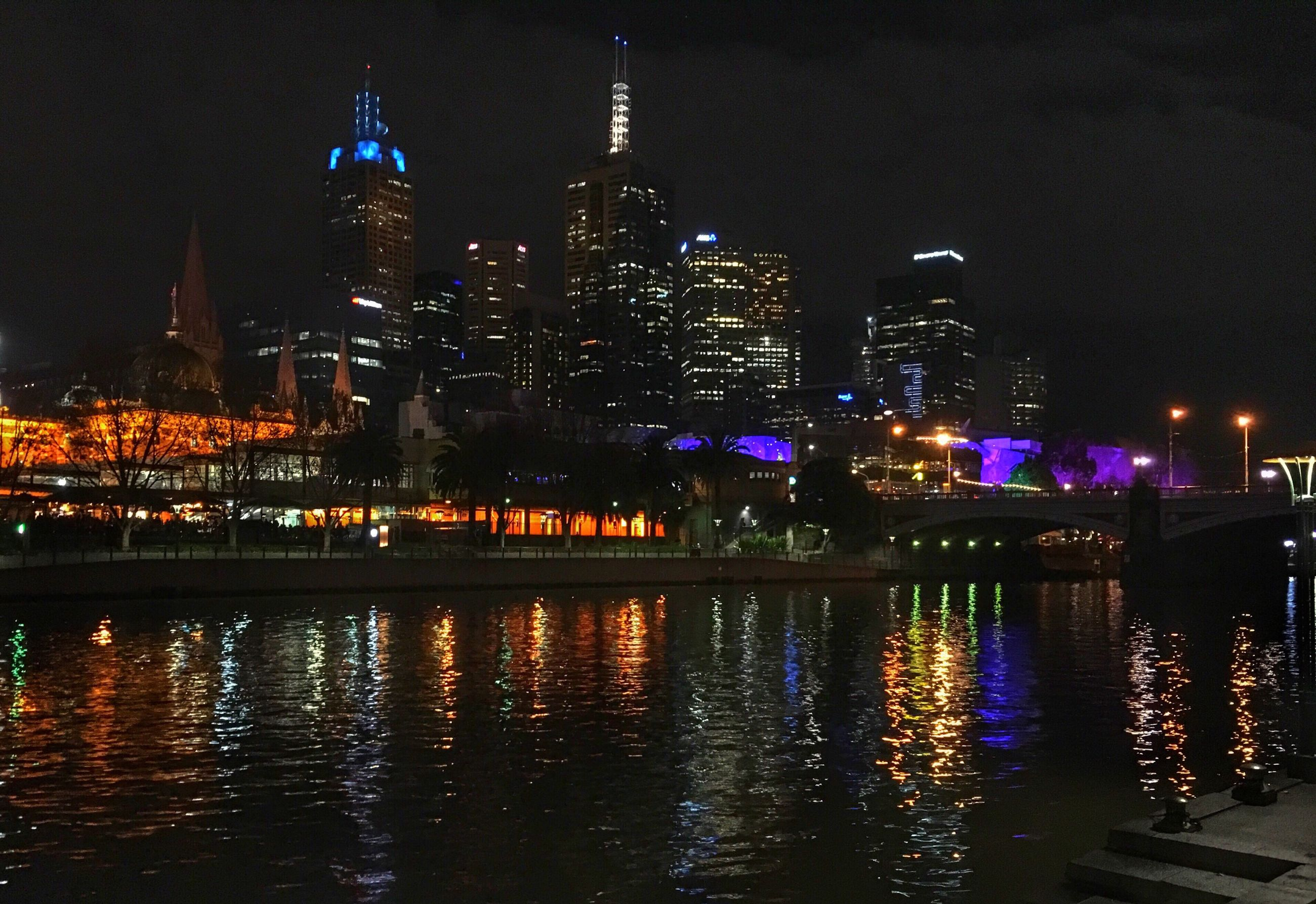 illuminated, night, building exterior, architecture, city, built structure, water, reflection, waterfront, river, cityscape, skyscraper, tower, tall - high, city life, modern, travel destinations, urban skyline, office building, capital cities