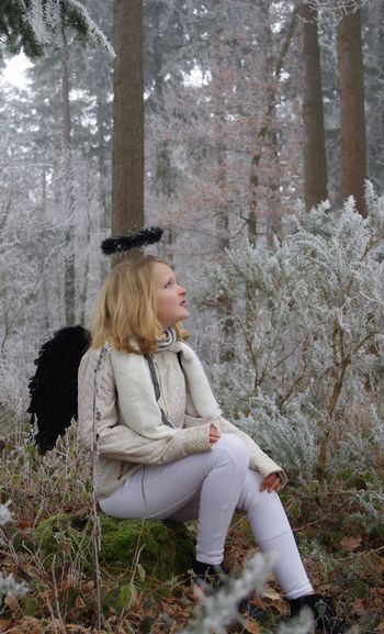 Young Woman Wearing Costume Wing And Halo Sitting On Rock At Forest During Winter