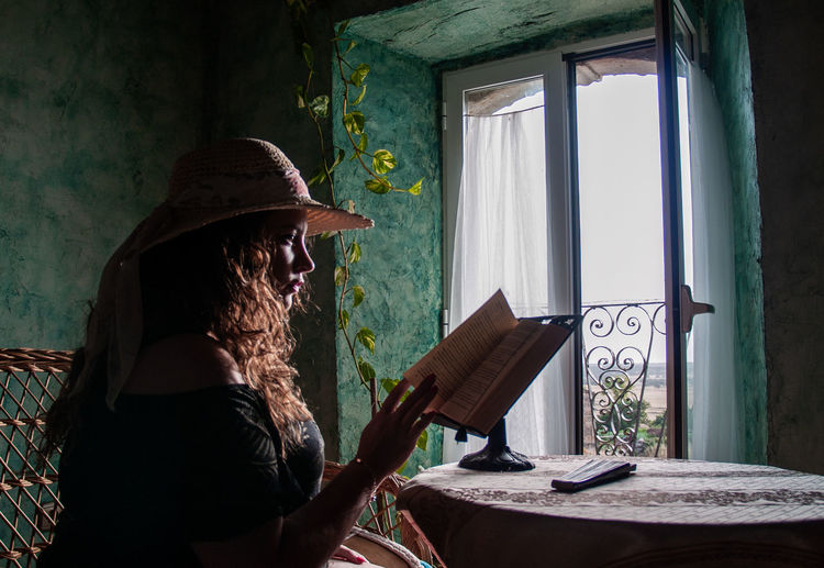 Woman Reading Book While Sitting By Table At Home